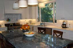 A kitchen with an island finished with a green granite countertop